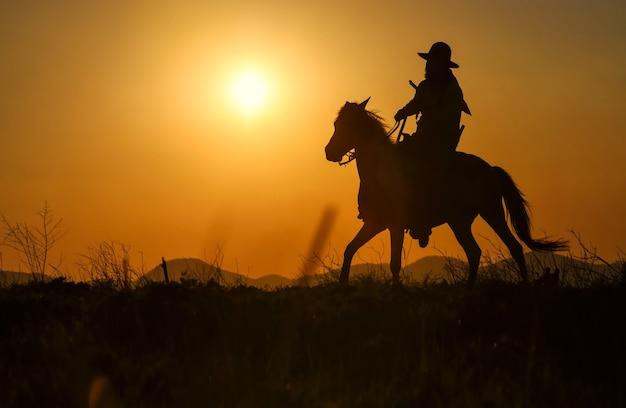 A silhueta de um homem vestindo um vestido de cowboy com um cavalo e uma arma na mão
