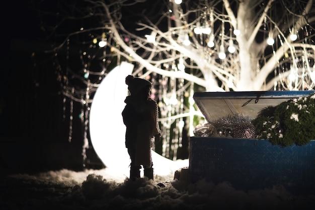 A silhueta de um menino com roupas de inverno perto do velho baú azul com brinquedos e árvore contra o natal