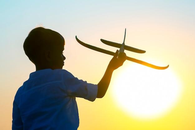 A silhueta de um menino permite que um modelo de avião voe para o céu, tendo como pano de fundo o sol poente. sonho infantil de um futuro piloto