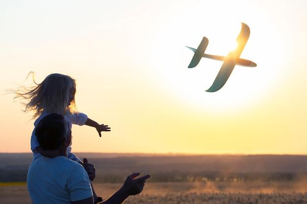 A silhueta de um menino sentado no ombro do pai lança um modelo de avião para o céu, tendo como pano de fundo o sol poente. o sonho de infância do futuro piloto