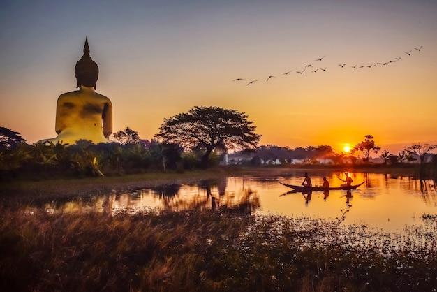 A silhueta de um monge e aluno está passeando de barco, indo receber esmolas em ang thong, na tailândia.