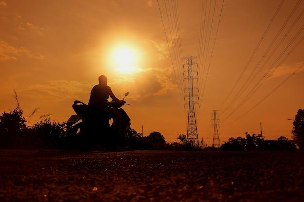 A silhueta de um motociclista na estrada que vê os eletrodos de alta tensão.