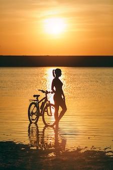 A silhueta de uma garota esportiva em um terno de pé perto de uma bicicleta na água ao pôr do sol em um dia quente de verão. conceito de aptidão.