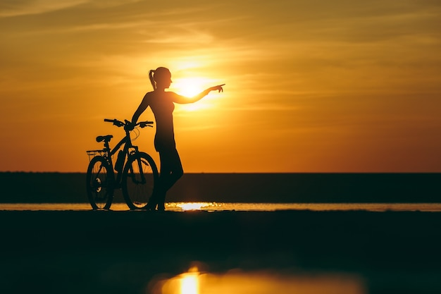 A silhueta de uma garota esportiva em um terno em pé perto de uma bicicleta na água e aponta a mão para a distância ao pôr do sol em um dia quente de verão. conceito de aptidão.