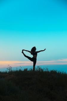 A silhueta de uma jovem praticando ioga