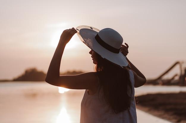 A silhueta de uma mulher ao pôr do sol a silhueta de uma jovem segurando a aba de um canudo ...