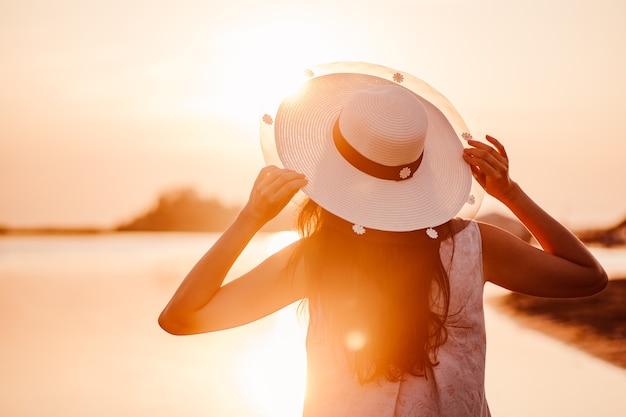 A silhueta de uma mulher ao pôr do sol a vista de uma mulher de cabelos escuros segurando a aba de um chapéu de palha ...