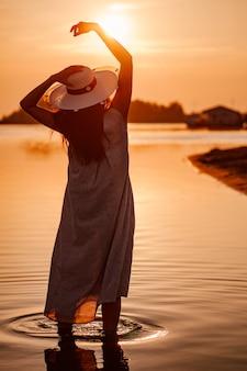 A silhueta de uma mulher ao pôr do sol uma silhueta de uma vista traseira de uma jovem com um chapéu de palha com ...