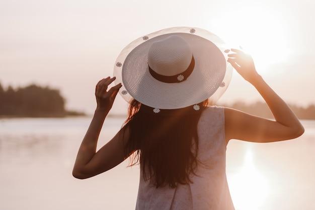 A silhueta de uma mulher na visão do pôr do sol de uma jovem segurando a aba de um chapéu de palha ...