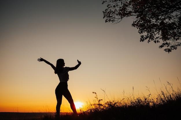 A silhueta de uma mulher solteira com a mão levantada usando uma selfie para tirar uma foto de si mesma ao pôr do sol.