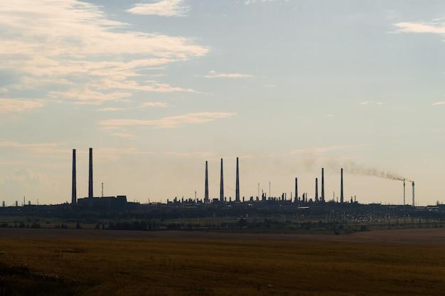 A silhueta de uma planta de processamento enorme do gás e de óleo com tochas ardentes, tubulações e destilação do complexo.