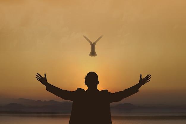 A silhueta do empresário levantou as mãos e orou a deus com um pombo voador no fundo do céu ao nascer do sol