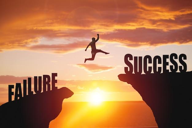 A silhueta do homem de negócios pula para o texto de sucesso sobre uma bela superfície de uma montanha com vista alta