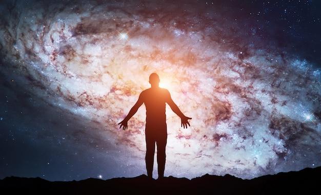 A silhueta do homem fica no topo da montanha e vê no céu noturno meditação e astrologia