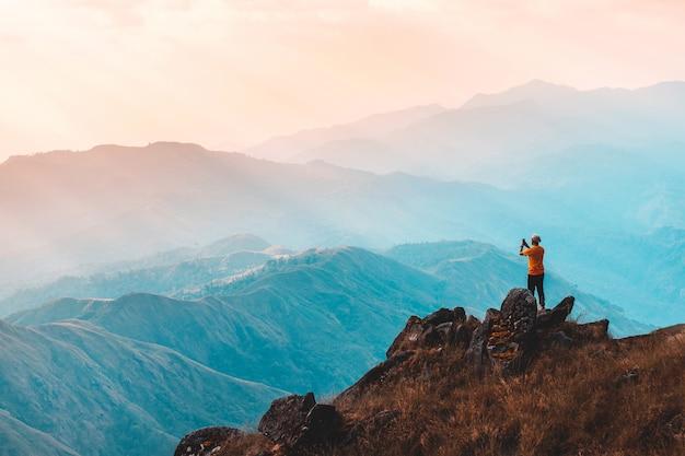 A silhueta do homem levanta as mãos no pico da montanha, conceito de sucesso