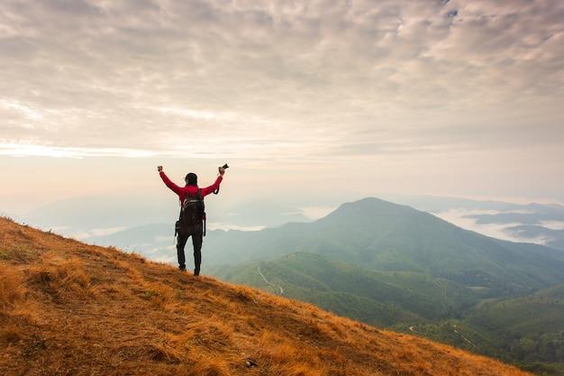 A silhueta do homem levanta as mãos no pico da montanha, o conceito de sucesso