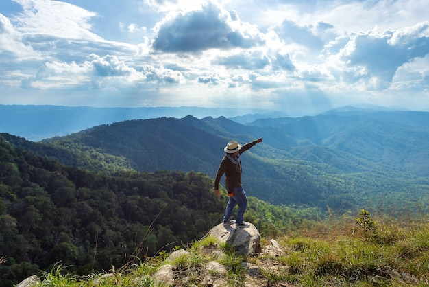 A silhueta do homem levanta as mãos no pico da montanha, o conceito de sucesso Foto Premium