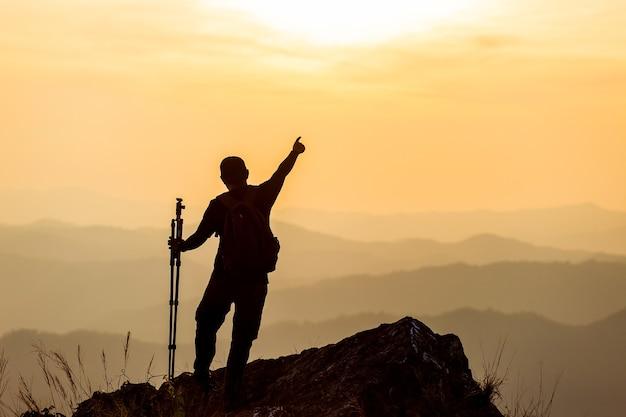 A silhueta do homem levanta as mãos no pico da montanha