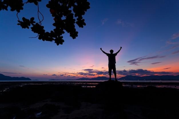 A silhueta do homem levantou as mãos com moldura de árvore no céu do pôr do sol ou nascer do sol.