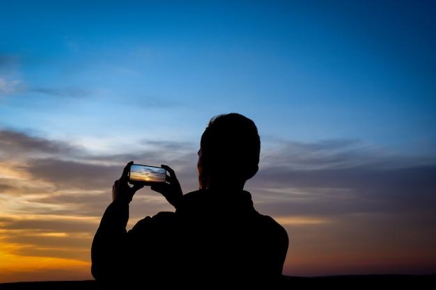A silhueta do homem novo dispara no por do sol no telefone, smartphone.