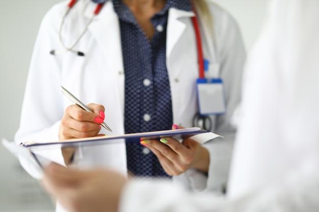 A silhueta do médico de jaleco branco está fazendo uma anotação em documentos na área de transferência