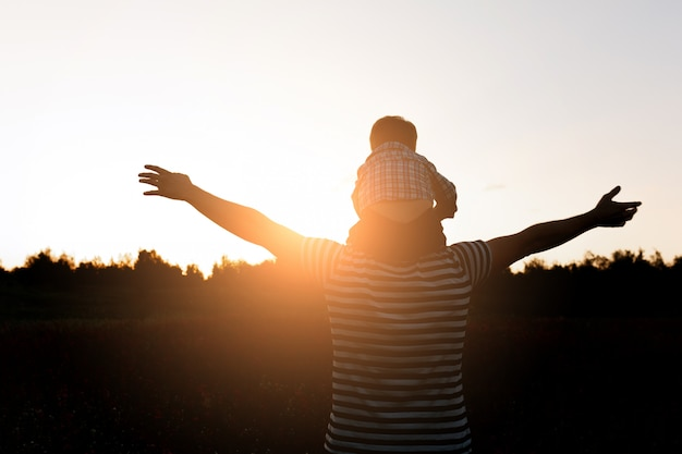 A silhueta do pai e do filho que anda no campo no tempo do por do sol, menino que senta-se equipa sobre os ombros. co