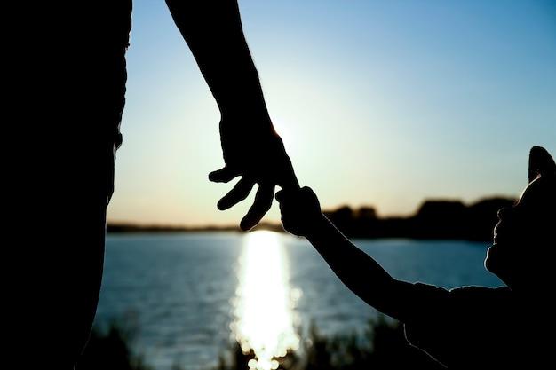 A silhueta do pai segura a mão de uma criança pequena