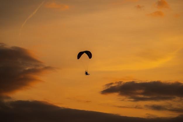 A silhueta do paramotor ao pôr do sol