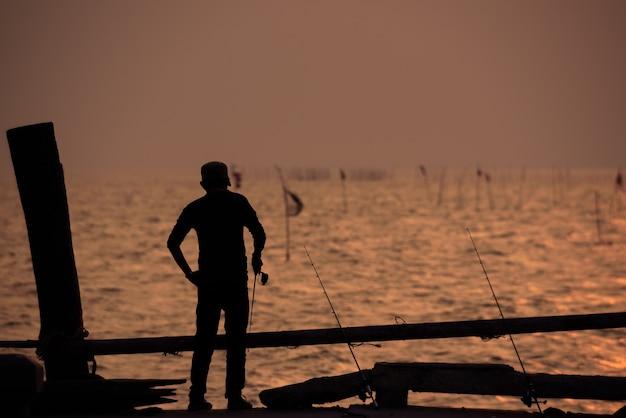 A silhueta do pescador com o pôr do sol