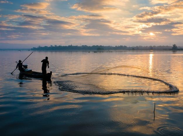 A silhueta do pescador jogando rede