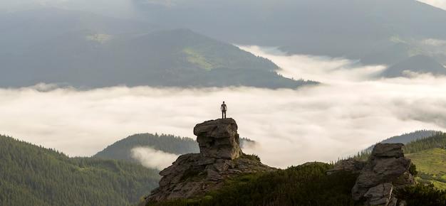 A silhueta do turista atlético do alpinista na formação rochosa alta no vale da montanha encheu-se com as nuvens inchadas brancas e a névoa e coberta com as inclinações de montanha sempre-verdes da floresta sob o fundo claro do céu.