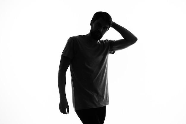 A silhueta escura de um homem gesticula com as mãos em um fundo branco
