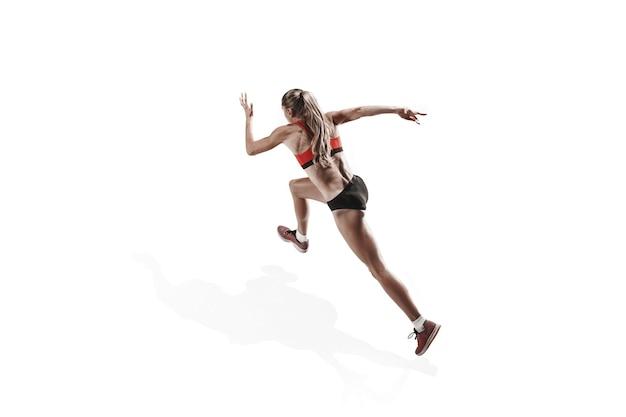 A silhueta feminina branca de um corredor correndo e pulando no fundo branco do estúdio