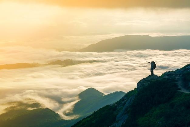 A silhueta pequena do turista com a trouxa na encosta da montanha rochosa com as mãos levantadas sobre o vale coberto com as nuvens inchadas brancas.