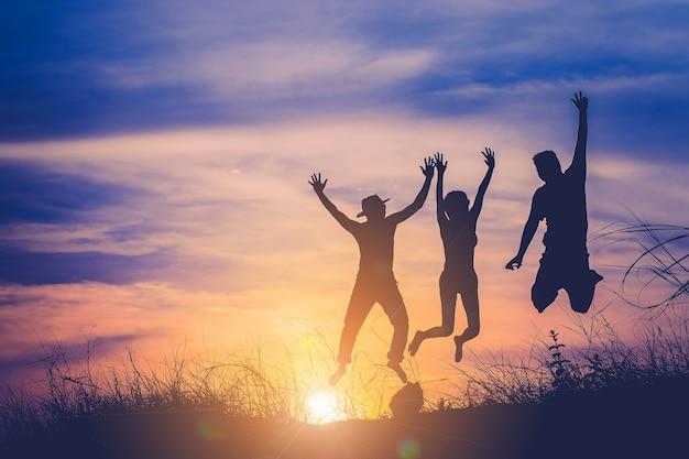 A, silueta, de, três pessoas, pular