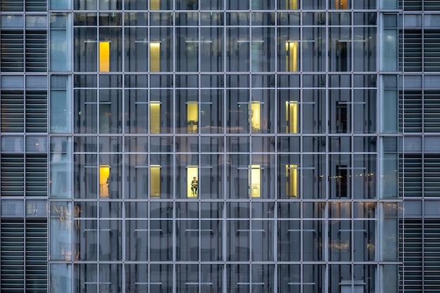 A simetria da construção offfce que têm funcionários trabalhando, tóquio, japão