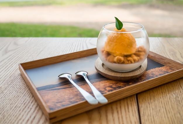 A sobremesa de laranja na mesa de madeira