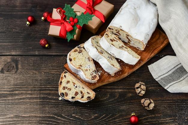 A sobremesa do ano novo do natal stollen cortada em uma tabela de madeira. receita de cozinha austríaca e alemã. natal na europa