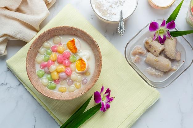 A sobremesa tailandesa chamou bolas de bualoy em colheres com leite de coco quente e folhas de pandan para aumentar a delícia.
