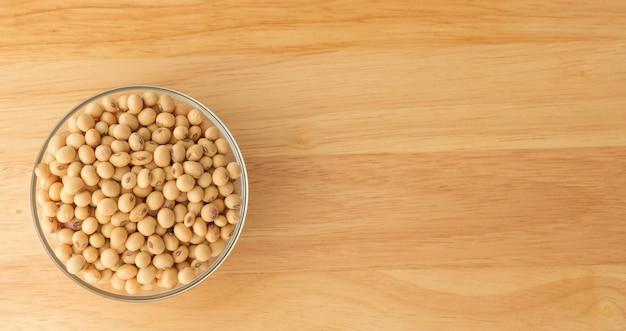 A soja está em um copo, colocado em uma mesa de madeira com copyspace, feijão amarelo