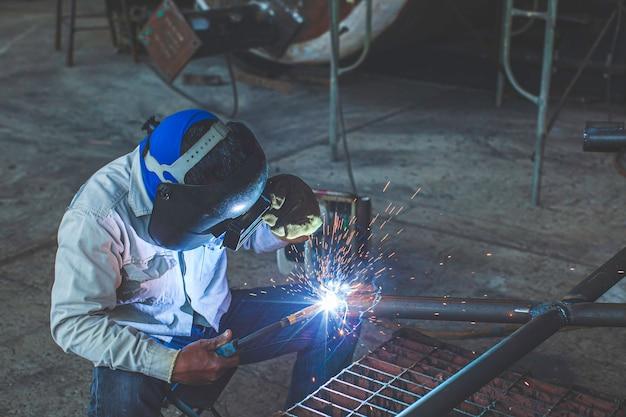 A soldagem de metal de trabalhador masculino faz parte da construção de um gasoduto de bocal de maquinário, petróleo e gás