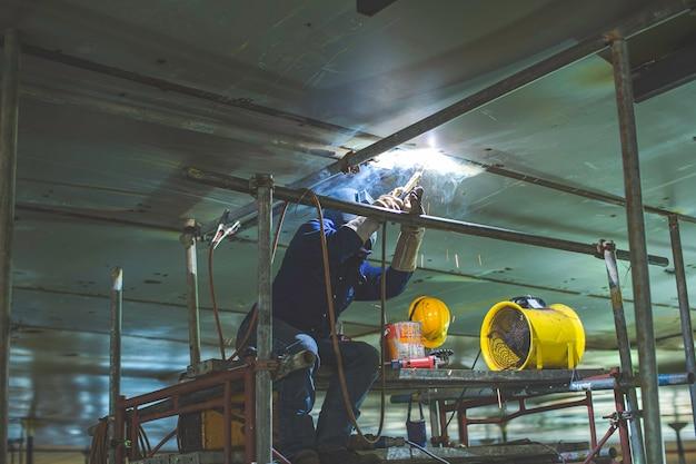 A soldagem do arco de metal do trabalhador masculino faz parte da construção do gasoduto do bocal do tanque de máquinas, óleo de petróleo e tanque de armazenamento de gás dentro de espaços confinados.