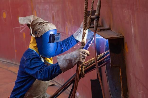 A soldagem do arco de metal do trabalhador masculino faz parte da construção do gasoduto do bocal do tanque de máquinas, óleo de petróleo e tanque de armazenamento de gás em espaços confinados.