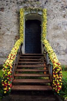 A solene porta da frente do castelo está decorada com rosas amarelas e escarlates