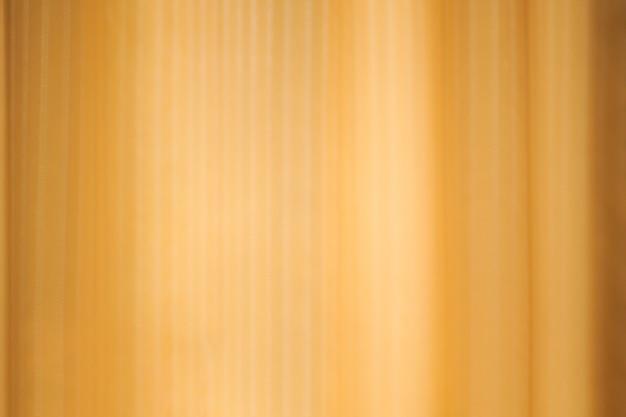 A sombra das cortinas transparentes em uma parede de ouro. projeto de textura de fundo de cortinas borradas