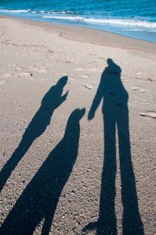 A sombra de um cachorro e seu dono na praia