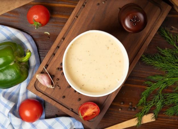 A sopa de cogumelo de creme na bacia descartável do copo serviu com vegetais verdes.