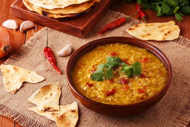 A sopa de lentilha vermelha indiana grossa com coentro serviu com pão liso indiano.