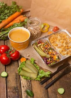 A sopa de lentilha vermelha na bacia descartável do copo serviu com vegetais verdes.