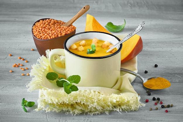 A sopa saboroso do creme da abóbora serviu com os croutons na luz - caneca amarela no guardanapo de harmonização.